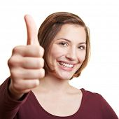 Charming smiling woman holding one thumb up