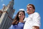 Young smiling couple stands on the background of blue sky near to Lomonosov Moscow State University