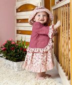 little child baby girl  standing near bed indoors in babyroom