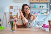 Young beautiful teacher woman wearing sweater and glasses sitting on desk at kindergarten clapping a poster