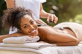 Young woman receiving hot stone massage at health spa and looking at camera. Portrait of relaxed afr poster