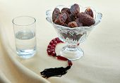 Ramadan breakfast of dates and water with prayer beads