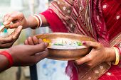 Religious Indian Woman Gives A Sacred Sweet Drink Called Charinamrita After A Religious Ceremony Cal poster
