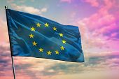 Fluttering European Union Flag On Colorful Cloudy Sky Background. European Union Prospering Concept. poster