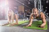 Sport Couple Doing Plank Exercise Workout In Fitness Centrum. Man And Woman Practicing Plank In The  poster