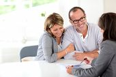 stock photo of contract  - Senior couple signing financial contract - JPG