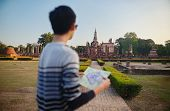 young thai male tourist with map at sukhothai historial park thailand poster
