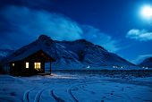 Landscape with a wooden house with light from the window in a winter night.  Scenic view of moonligh poster