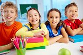 foto of diligent  - Portrait of cheerful school children flashing toothy smiles - JPG