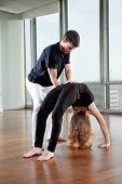 Yoga instructor making adjustment to woman's Bridge Pose at gym