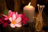 Wellness and spa concept with candles, frangipani flower, sandalwood and rattan sticks on massage ta