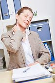Elderly business woman feeling pain in her neck in her office