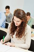 Happy female student taking notes in university course classroom