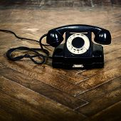 vintage old telephone, black retro phone is on the floor of used parquet