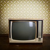 retro tv with wooden case in room with vintage wallpaper and parquet