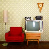 Vintage room with wallpaper, old fashioned armchair, retro tv, phone, clocks, radio player and stand