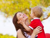 Happy young mother playing game with cute little son outdoors in spring time, cheerful child with mo