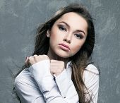 Young woman with estrangement emotion over grey background
