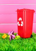 Recycling bin with papers on grass on pink background