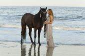 mujer en vestido formal en el océano con caballo, tiempo de exposición que muestra el movimiento de las olas