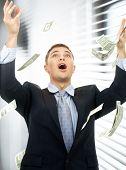 feliz hombre de negocios exitoso en lluvia de dinero en el interior