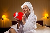 Smiling woman with gift sitting on bed at Valentines day