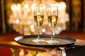 Waiter served champagne glasses on a tray in a fine dining restaurant, a large chandelier is in Back