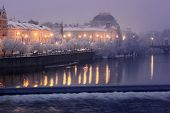 view on snow Smetanovo Embankment and National Theatre in Prague before dawn, Czech Republic