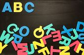 Alphabet magnets in a jumble on blackboard with Abc in order at the top