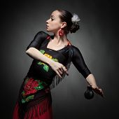 image of castanets  - young woman dancing flamenco with castanets on black - JPG