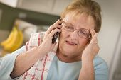 Shocked Senior Adult Woman on Her Cell Phone in Kitchen.