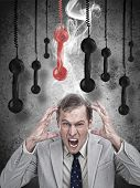 Stressed out businessman with phone receivers hanging down