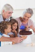 Children with their grandparents icing a cake in the kitchen