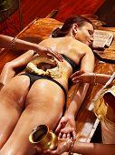 Woman having oil Ayurveda spa treatment of back pain.