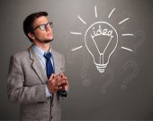 Attractive young boy comming up with a light bulb idea sign