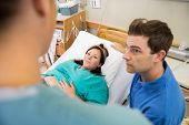High angle view of mid adult pregnant woman and husband looking at nurse in hospital room