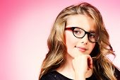 Portrait of a beautiful ten years girl in spectacles smiling at camera. Pink background.