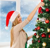 christmas, x-mas, winter, happiness concept - smiling woman in santa helper hat decorating a christm