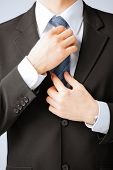 business people and office concept - close up of man adjusting his tie