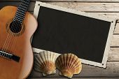 stock photo of serenade  - Acoustic brown guitar and aged photo frame with two sea shells on beach wooden floor over summer sand - JPG