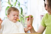 stock photo of crying boy  - Crying baby boy refusing to eat food from spoon with hands dirty of vegetable puree - JPG