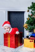 Boy dressed as Santa sitting in a gift box