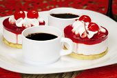 Cherry cakes with coffee on a plate