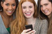 Close up portrait of cheerful young female friends with mobile phone together at home