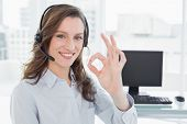 Businesswoman wearing headset while gesturing ok sign in front of computer in a bright office