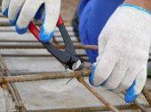 stock photo of bender  - Closeup shot of bar bender hands fixing steel reinforcement bars using pincers - JPG