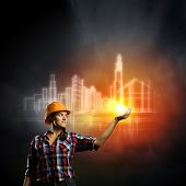 Image of woman in hardhat pushing icon of media screen