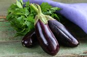 stock photo of aubergines  - ripe purple eggplant on a wooden background - JPG