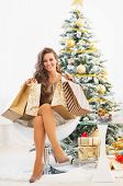 Full Length Portrait Of Happy Young Woman With Shopping Bags Near Christmas Tree