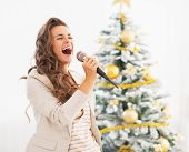 Happy Young Woman Singing Near Christmas Tree